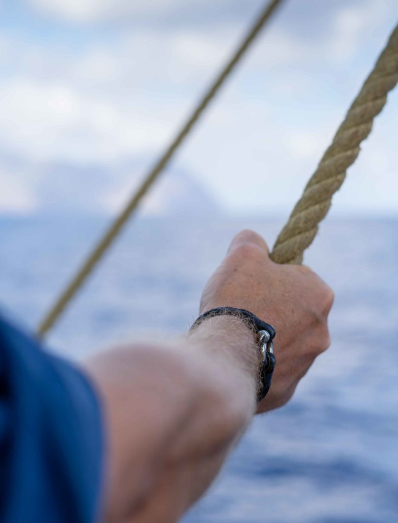 Maritimes Lederarmband an Herrenhandgelenk, Blick aufs Meer